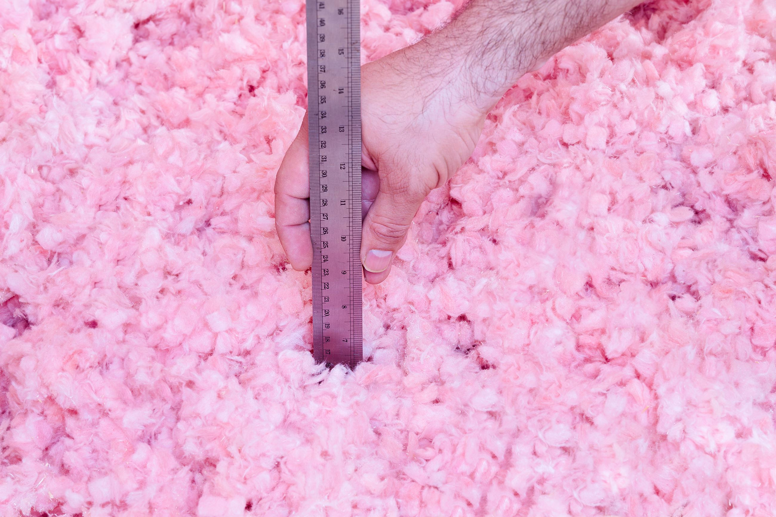 Image of a ruler demonstrating the height of the insulation in the home's attic